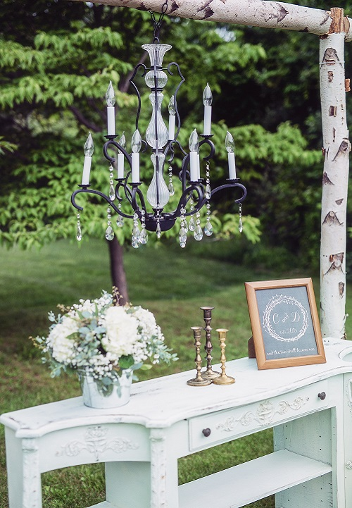 Rustic vintage outdoor ceremony altar with birch wood, chandelier and gold candle stick holders