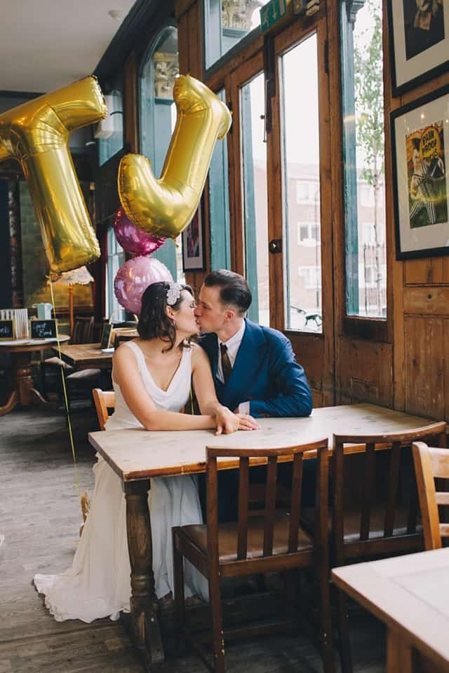 Bride and groom kissing with gold balloon initials above them