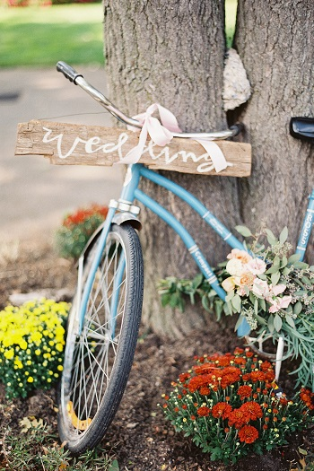 bike with wood wedding sign against tree