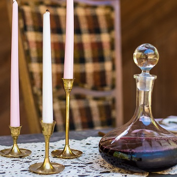 Vintage brass candle holder with lace table runner and decanter on wedding reception table