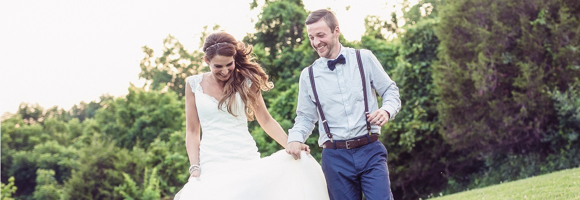 bride and groom running in green field captured by dp photo