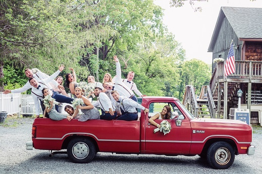 bride driving red ford truck with bridal party in the back