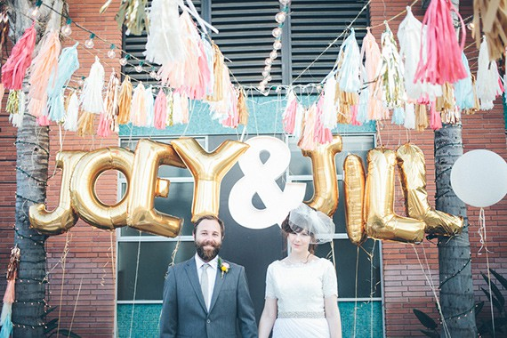 Bride and groom posing in front of gold balloons names