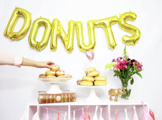 Gold balloons spelling DONUTS