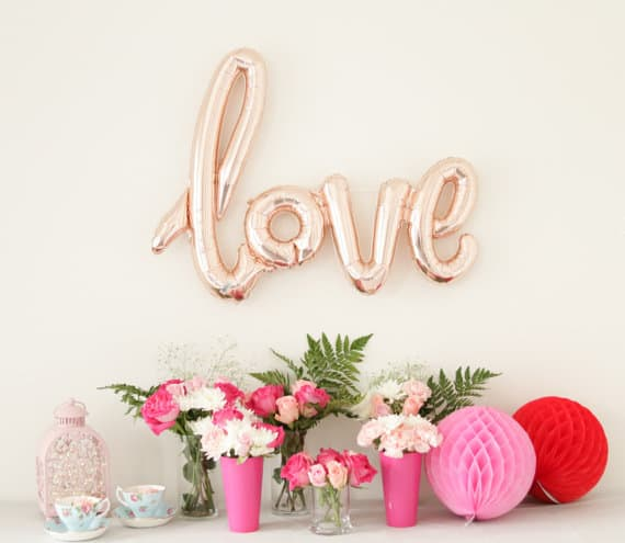 Rose gold balloon spelling LOVE in calligraphy