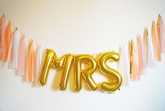 Gold foil balloons spelling out MRS