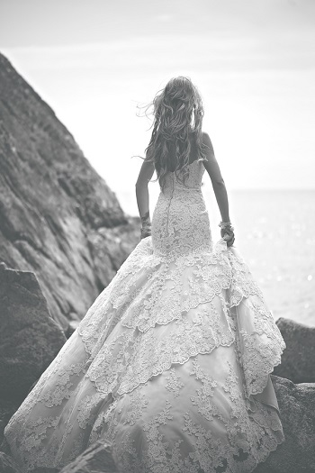 Black and white photo of bride standing on Whytecliff Park rocks