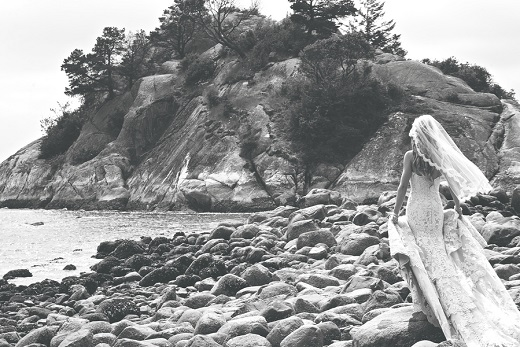 Black and white photo of bride walking on the beach