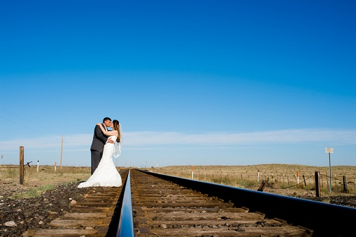 Bride and groom kissing on train tracks