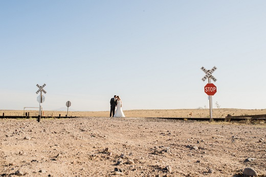 Bride and groom kissing on train tracks in hot sun