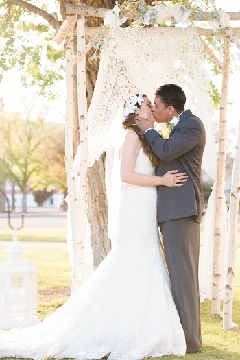 Bride and groom kissing under Rustic Birch Altar for wedding at Presidio County Courthouse