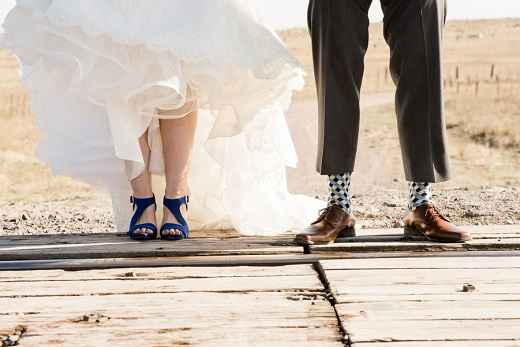 Bride and groom standing on train tracks captured by Artistic Imagez