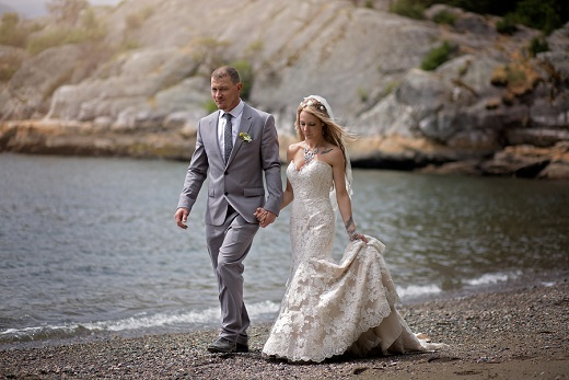 Bride and groom walking along the beach captured by Karizma Photography