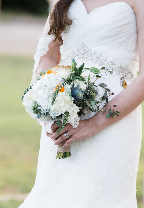 Bride holding white hydragea bouquet with purple thistles