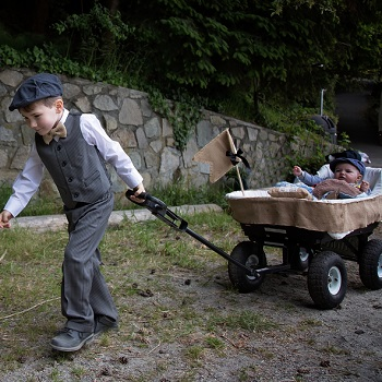 Ring bearer pulling baby in a rustic themed burlap wagon