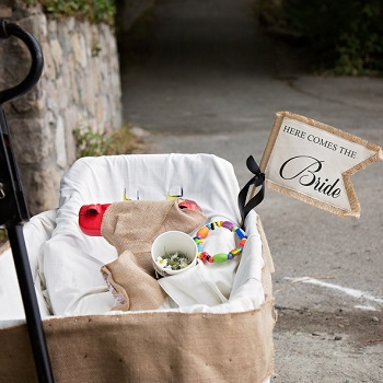 Rustic Burlap themed wagon with a here comes the bride sign
