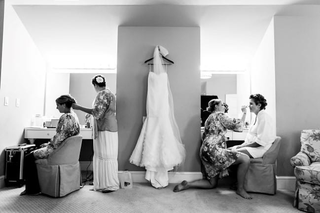 black and white photo of chapel length veil hanging with dress while brides do makeup