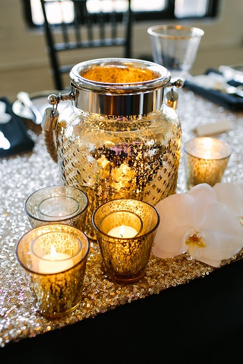 Wedding reception table with mercurtry class candle lanterns on a sequin table cloth