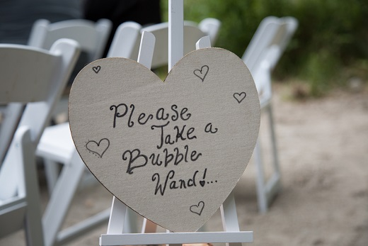 Wedding sign in the shape of a heart asking guest to take bubbles