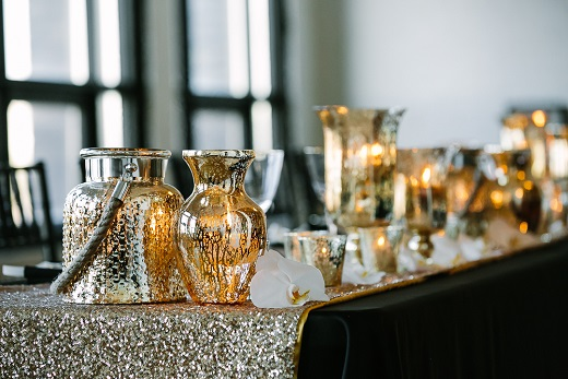 black wedding reception table with gold sequin table runner and mercury glass lanterns