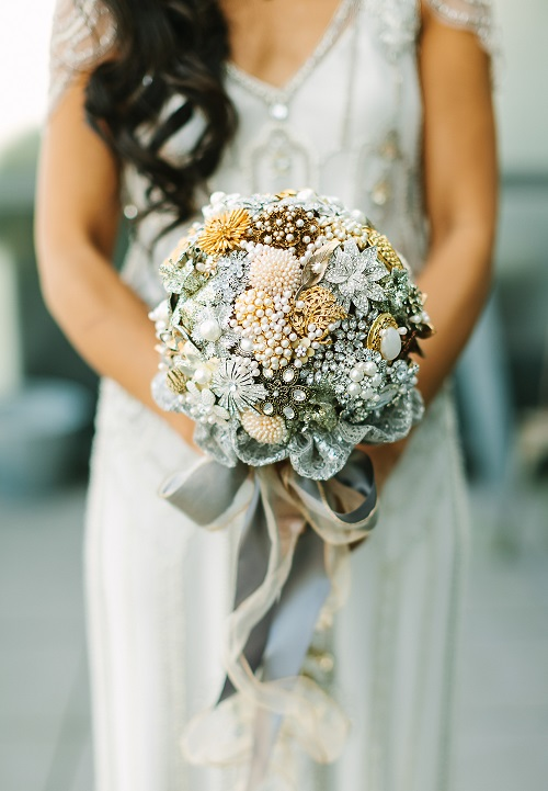 bride carrying a silver broach bouquet