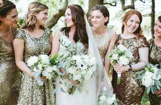 bride standing with bridesmaids wearing glittery gowns