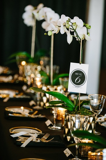 gold and black wedding reception table with white ochids