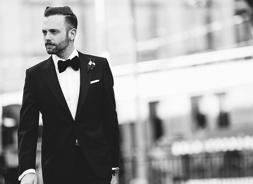 groom wearing tux walking down the street captured by A Brit & A Blonde