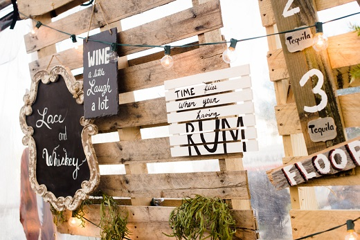 rustic outdoor wedding reception with drink quotes hanging from the wall