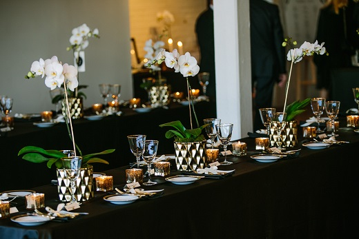 wedding reception table with gold and black decor and whtie4 orchids