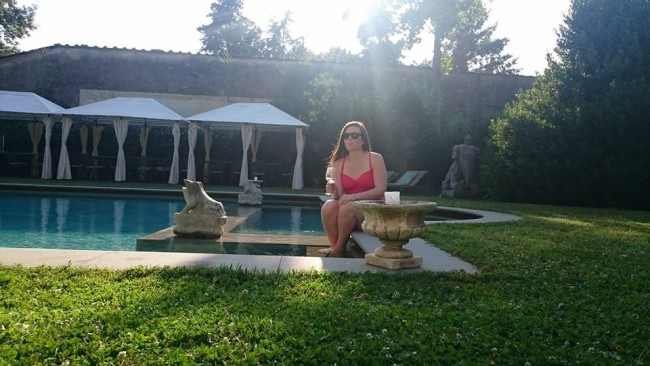 wearing sunglasses and sipping wine poolside in the Tuscan sun