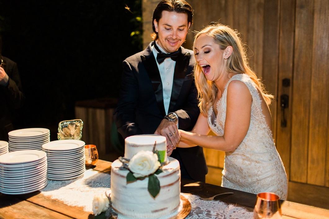 Bride and groom cutting cake captured by Kaitie Brainerd Photography