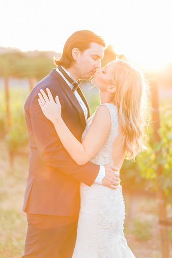 Bride and groom kissing in vineyard captured by Kaitie Brainerd Photography