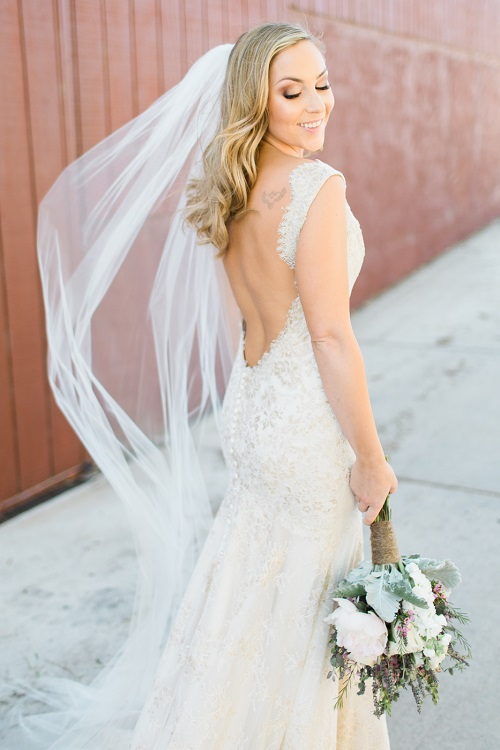 Bride posing in a floor length veil holding a bridal bouquet with rustic flair