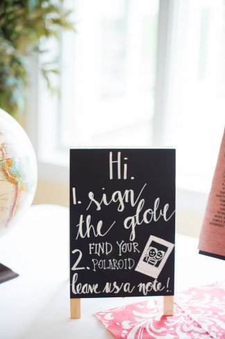 Chalkboard sign asking their guests to sign their globe guestbook
