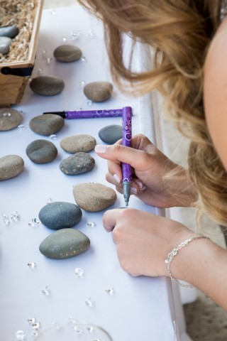 Wedding guest signing a rock for wedding guest book