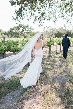 bride walking towards groom in Brander Vineyards