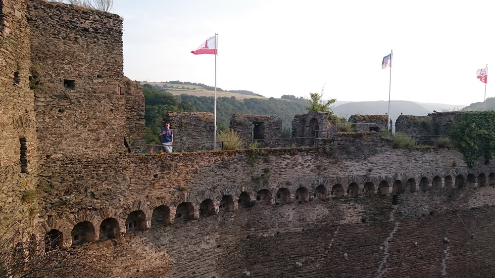 view of stone wall remains with flags atop Castle Schoenburg
