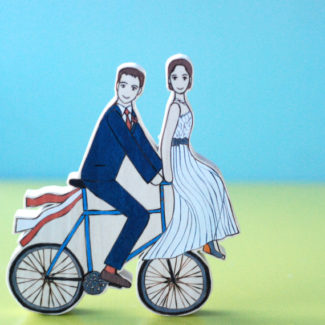 Wooden wedding cake topper with bride and groom on a bike