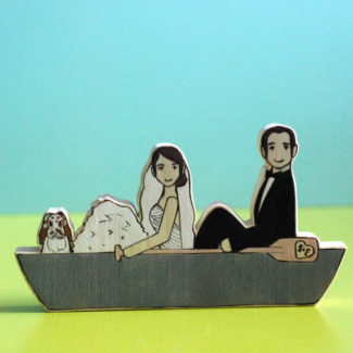 Wooden wedding cake topper with bride and groom in a row boat
