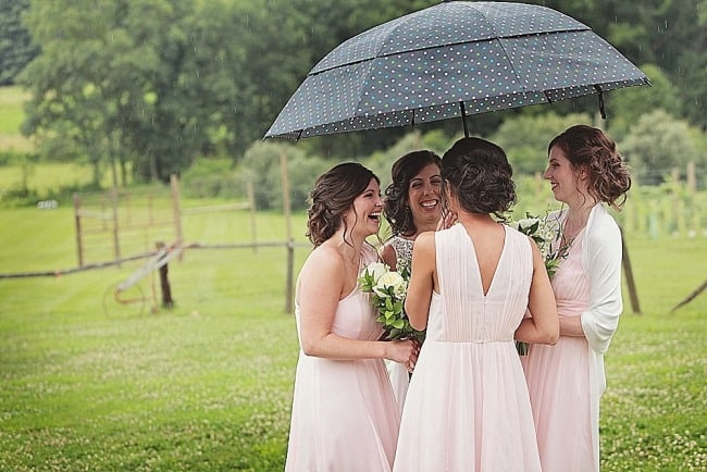 Bride standing under black with white polka dot umbrealla with bridesmaids