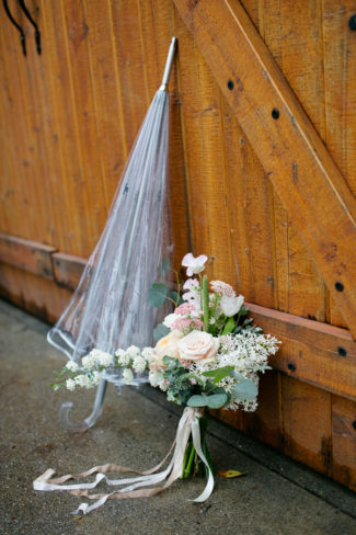 clear-umbrella-learning-against-a-wooden-wall-with-loose-floral-arrangement