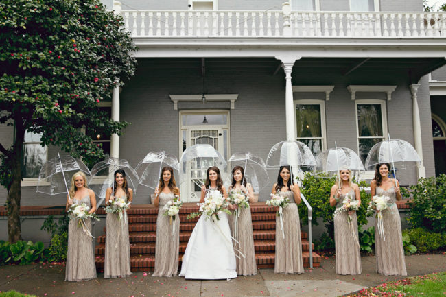 Bride standing with bridesmaids in the rain holding clear bubble umbrellas