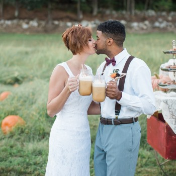 couple-kiss-while-holding-large-mason-jars