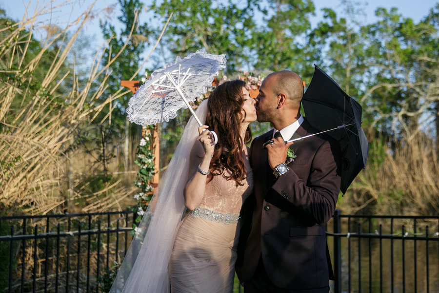 newlyweds each hold an umbrella in the sun