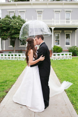 kissing under clear wedding umbrella