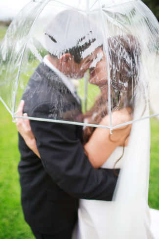 newlyweds kiss under clear umbrella