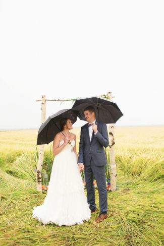newlyweds with black umbrellas in field