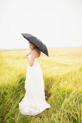 bride with black umbrella in field