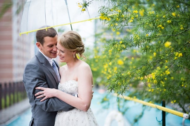 Bride and groom embracing under clear umbrella with yellow trim